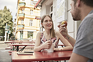 Smiling woman looking at man at a sidewalk cafe - SUF00101
