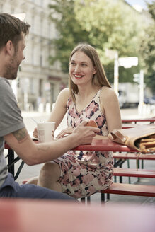 Smiling woman looking at man at a sidewalk cafe - SUF00104