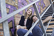 Happy couple sitting on stairs outdoors - SUF00110