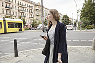 Woman in the city holding cell phone - SUF00122