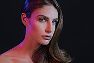 Portrait of bare-chested young woman in front of black background - SHKF00686
