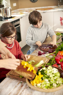 Boy and girl chopping vegetables in the kitchen - TSFF00132