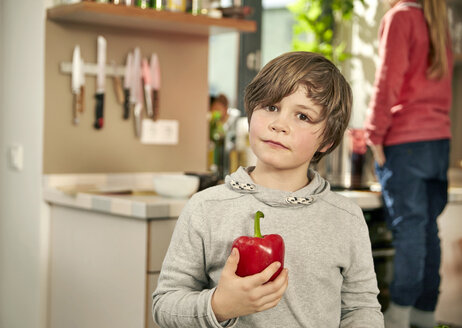 Portrait of boy standing in kitchen with red bell pepper - TSFF00138