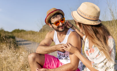 Tender couple in love wearing straw hats and sunglasses - MGOF02574
