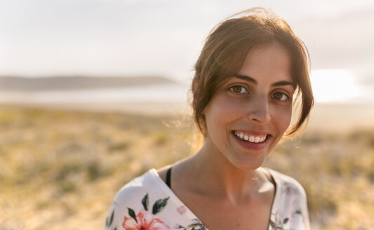 Portrait of smiling woman near the coast at evening sunlight - MGOF02586