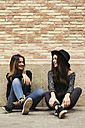 Two best friends sitting in front of facade talking together - EBSF01856