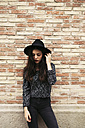 Fashionable young woman wearing black hat standing in front of facade - EBSF01865