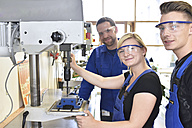 Portrait of smiling instructor with trainees at drill machine - LYF00627