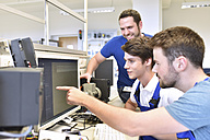 Technical instructor and students looking at computer screen - LYF00633