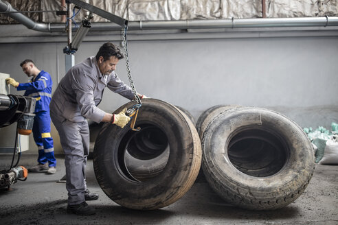 Tire repairer checking tire in factory - ZEF11145