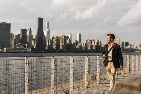 USA, New York City, businessman walking along East River - UUF08847