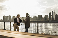 USA, New York City, two businessmen talking at East River - UUF08856