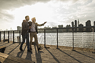 USA, New York City, two businessmen walking together along East River - UUF08859