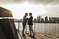 USA, New York City, two businessmen meeting at East River - UUF08865