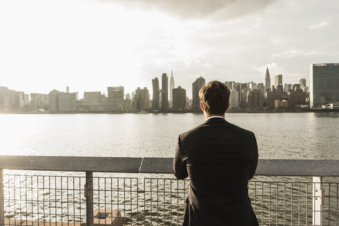 USA, New York City, back view of businessman looking at skyline of Manhattan - UUF08868