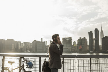 USA, New York City, businessman at East River on cell phone - UUF08874