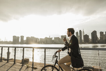USA, New York City, businessman on bicycle with takeaway coffee - UUF08886