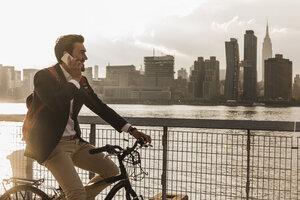 USA, New York City, businessman on bicycle talking on cell phone - UUF08889