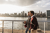 USA, New York City, two young men walking along East River - UUF08898