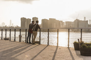 USA, New York City, two young men talking at East River - UUF08901