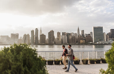 USA, New York City, two young men walking along East River - UUF08904