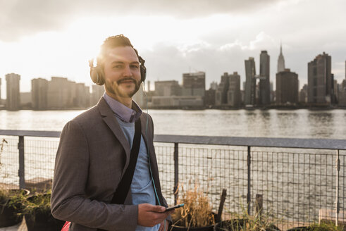 USA, New York City, portrait of smiling young man with headphones and cell phone - UUF08910