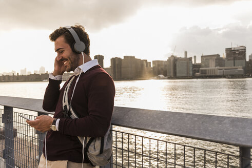 USA, New York City, smiling young man with headphones and cell phone at East River - UUF08913