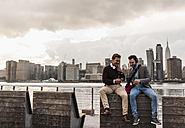 USA, New York City, two young men with headphones and cell phone sitting at East River - UUF08919