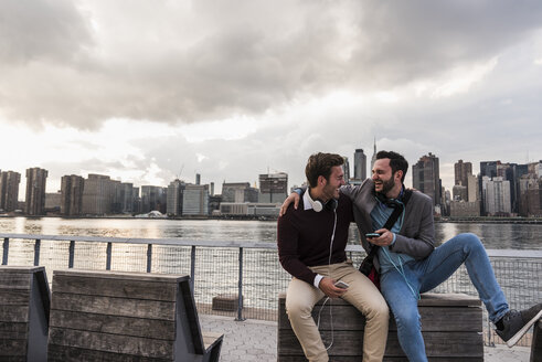 USA, New York City, two happy young men with headphones and cell phone sitting at East River - UUF08922