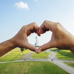 Germany, Duesseldorf, hands forming a heart framing Rhine Tower - KRPF01931