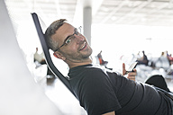 Man sitting in airport departure area, holding smart phone - SHKF00693