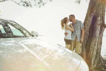 Couple on a road trip taking a break kissing each other - SHKF00699