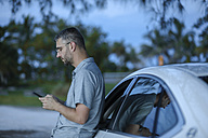 Man using smart phone GPS leaning against his car - SHKF00705