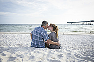 USA, Kissing couple sitting at Panama City Beach - SHKF00711
