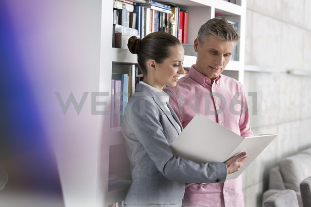 Smiling businesswoman and man looking at folder - LOF04564