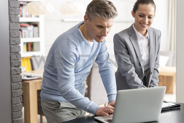 Man and businesswoman using laptop together - LOF04573