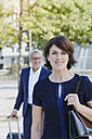 Smiling businesswoman on the go with businessman in background - RORF00387