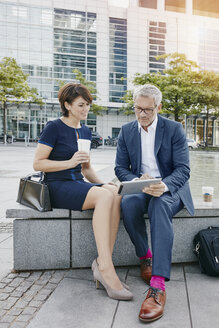 Businessman and businesswoman with digital tablet outdoors - RORF00390