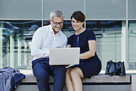Businessman and businesswoman sitting on bench sharing laptop - RORF00423