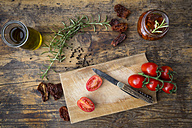 Glass of pickled dried tomatoes and ingredients on wood - LVF05533