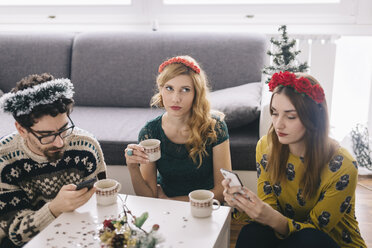 Annoyed young woman sitting between her friends looking at her smartphones - LCUF00068