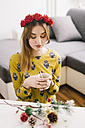 Young woman wearing floral wreath relaxing with cup of coffee at home at Christmas time - LCUF00071