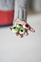 Woman holding artificial sweets eyes - CHPF00299