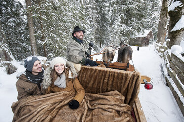 Couple enjoying a ride in a horse-drawn sleigh in winter - HHF05461