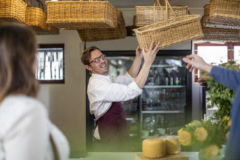 Grocer presenting wickerbasket in a farm shop - ZEF11262