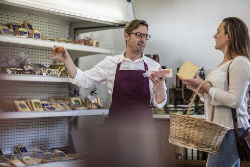Grocer selling cheese in a grocery store - ZEF11274