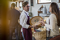 Grocer talking to customer in a farm shop - ZEF11277