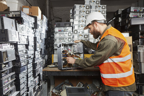 Worker in computer recycling plant dismounting desktop pc - RKNF00378