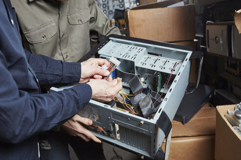 Worker in computer recycling plant dismantling desktop pc - RKNF00396