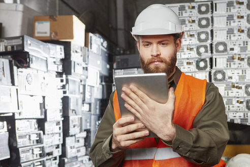 Worker in computer recycling plant using digital tablet - RKNF00411